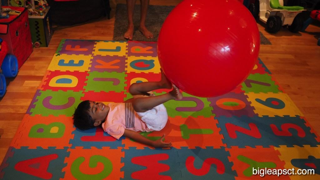 kid kicking pilates ball
